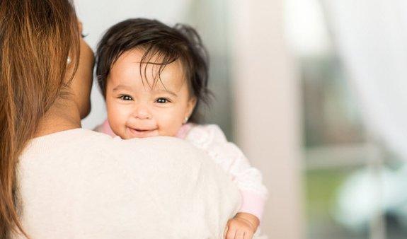 Baby looking over woman's shoulder