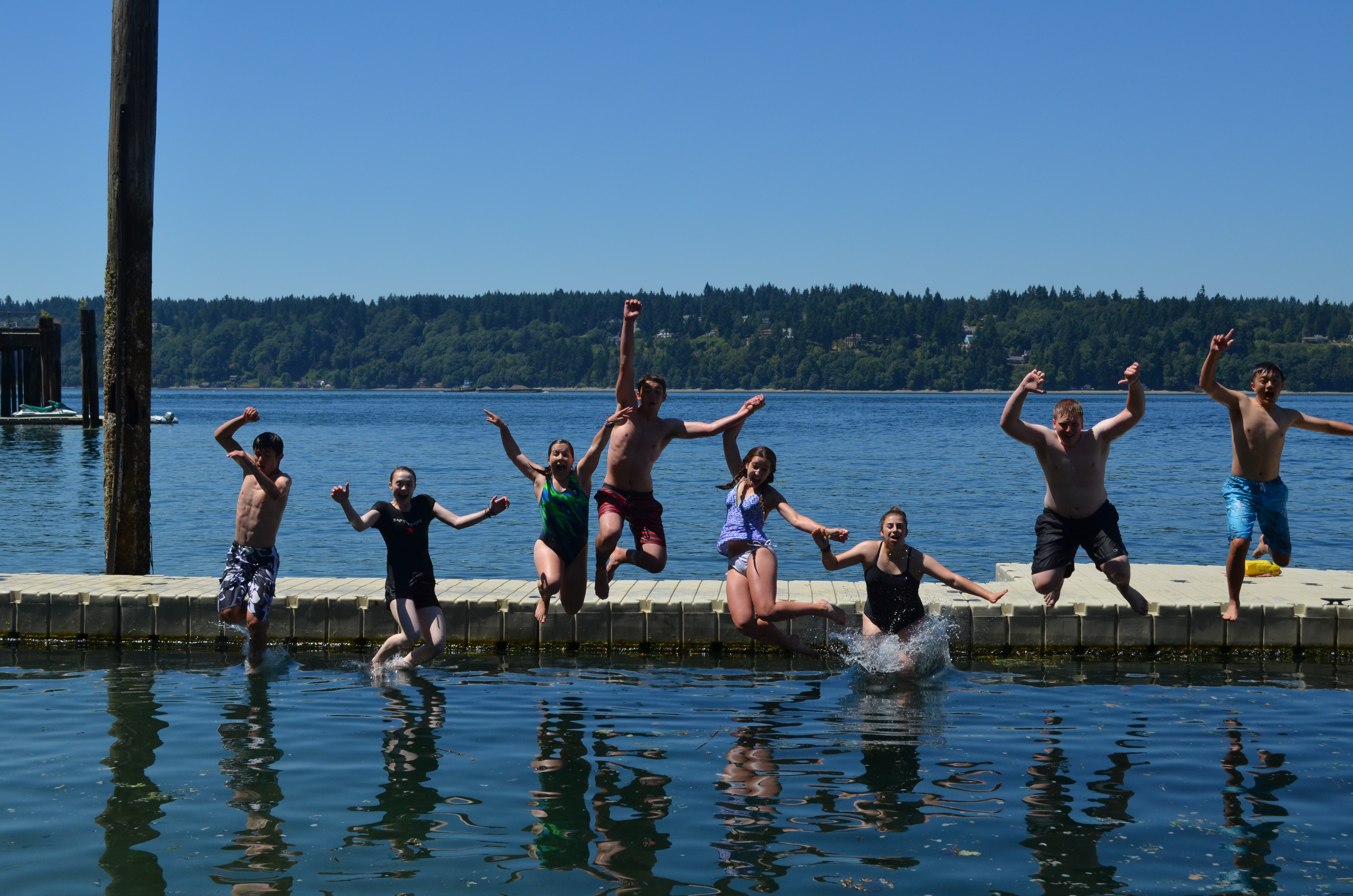Swimmers jumping off the dock at Camp Sealth