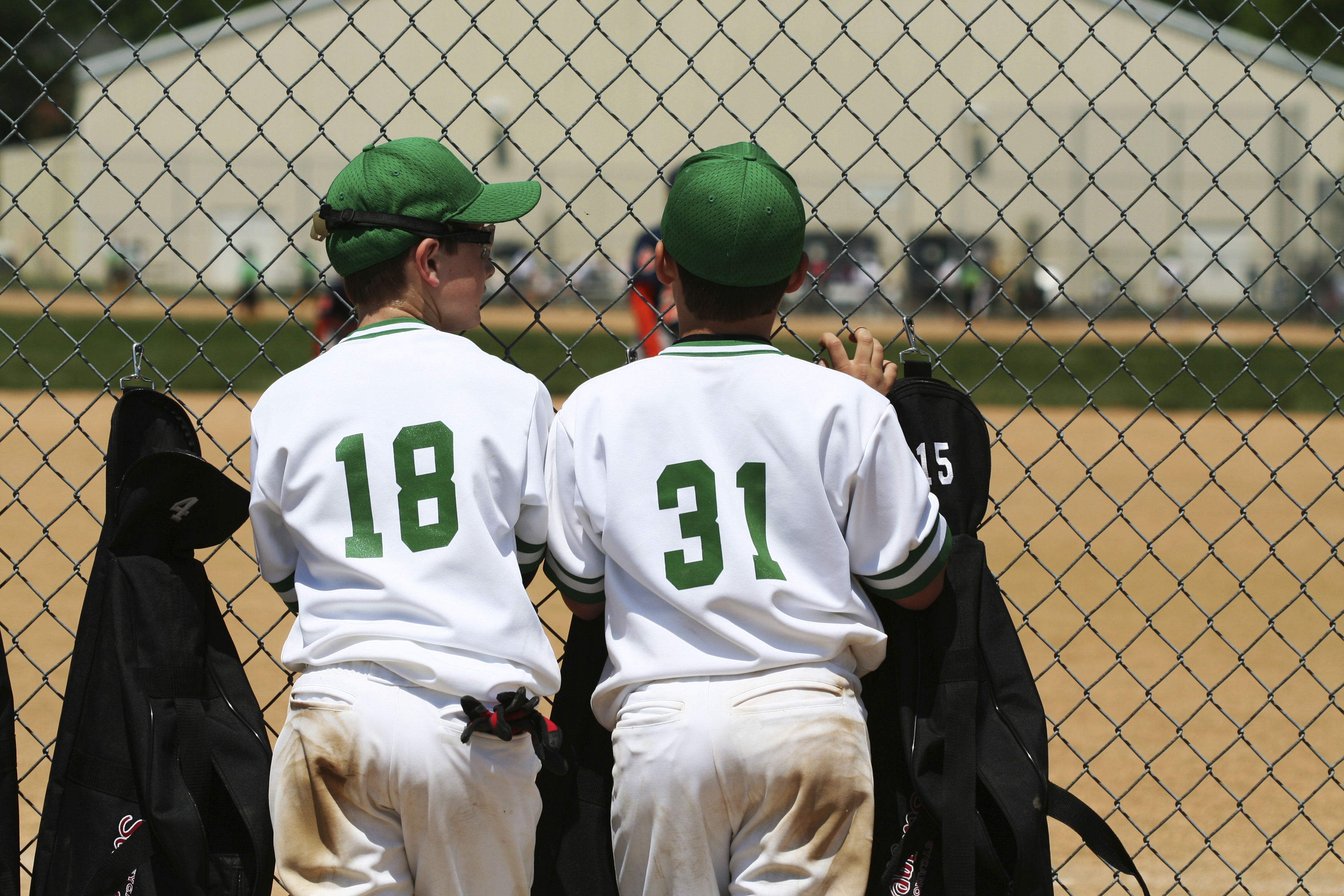 two boys in white and green baseball uniforms