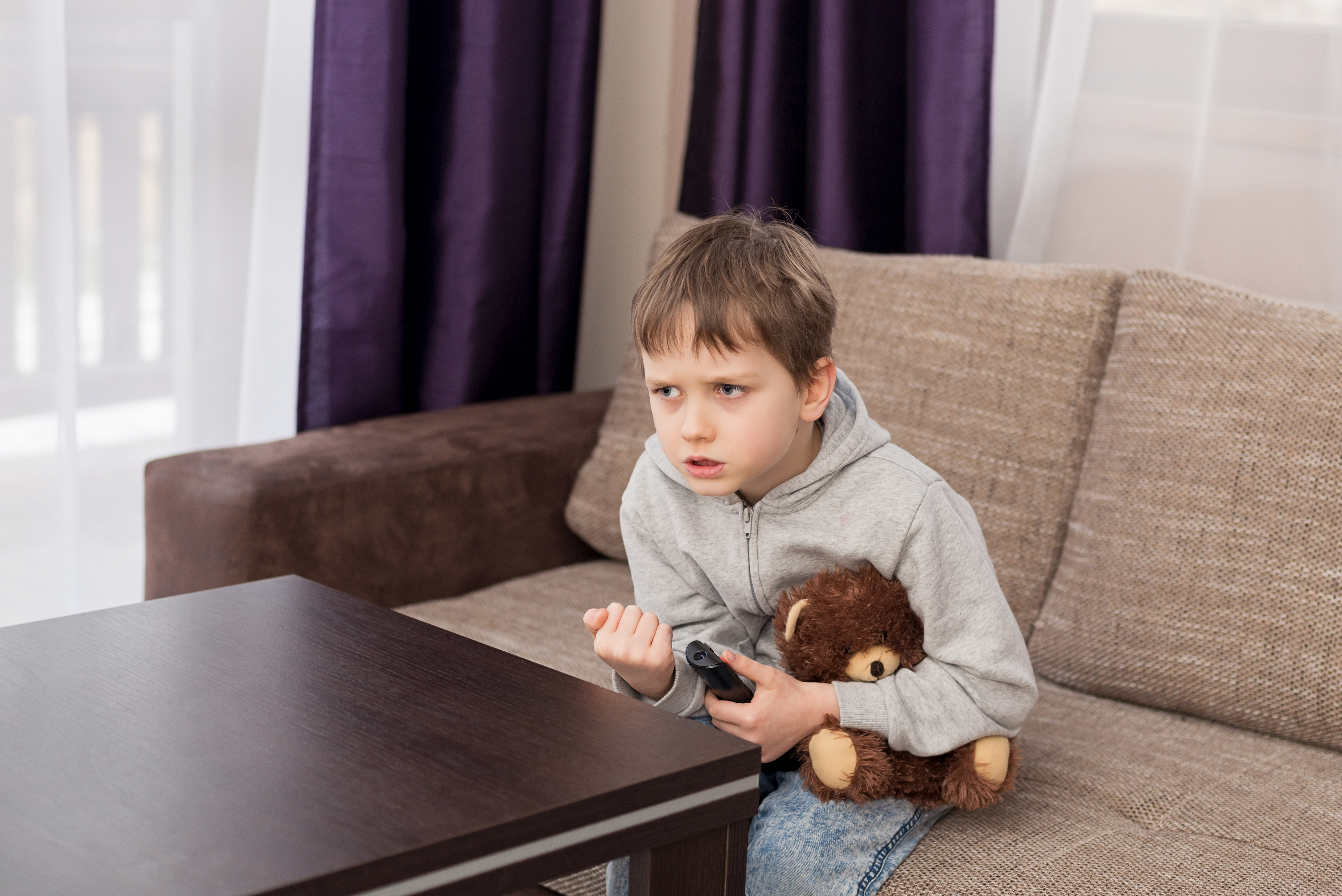 Little boy holding teddy bear and watching TV, looking stressed