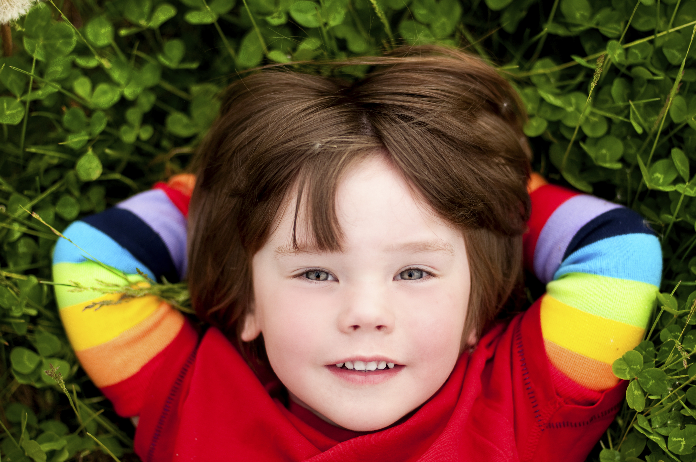 Small child in the grass wearing rainbow sleeves