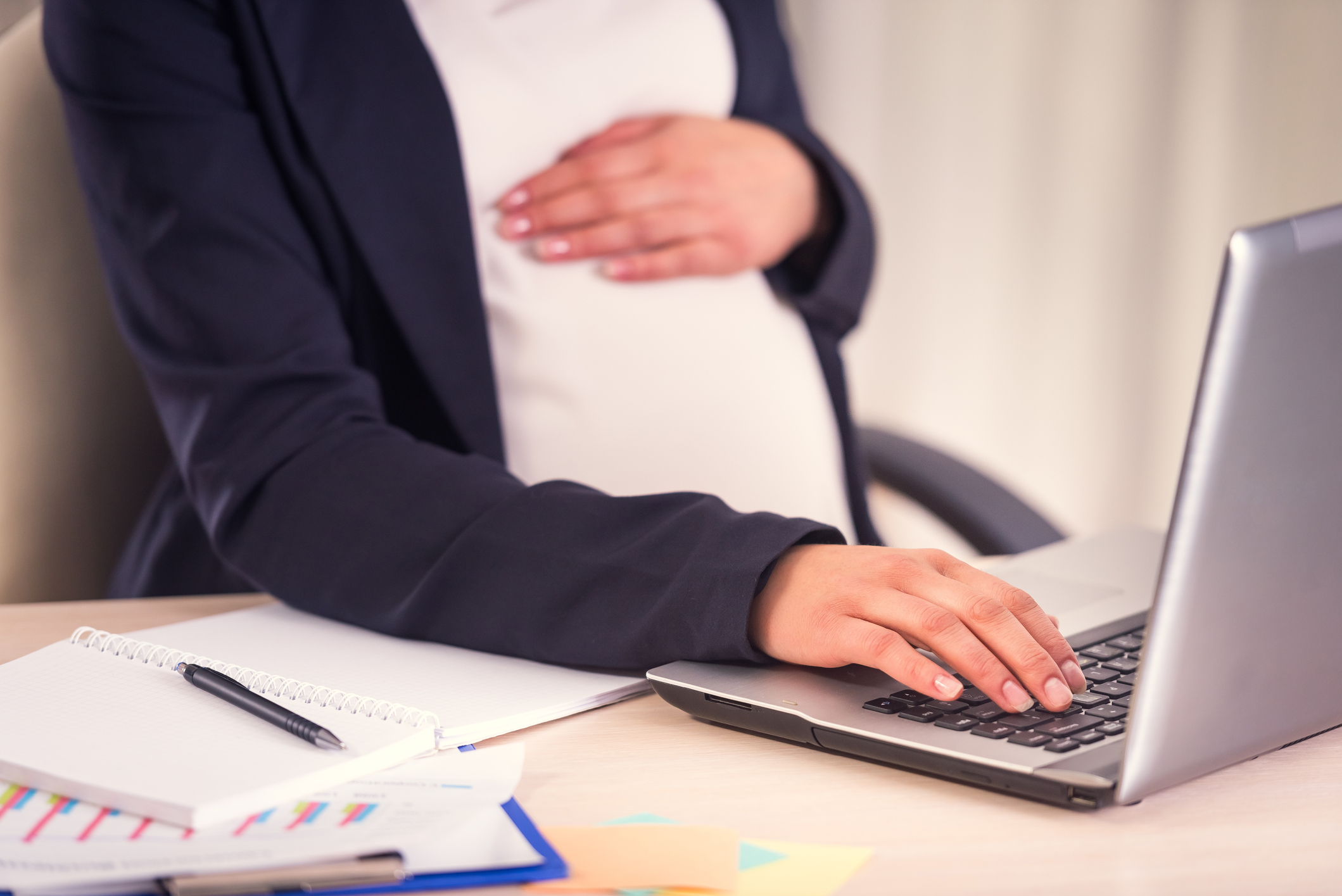 Pregnant woman with hand on stomach working at a computer