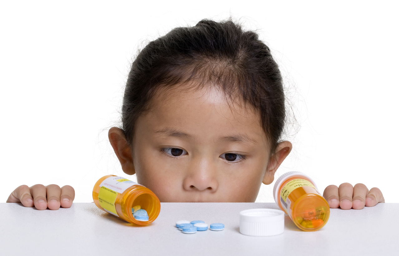 little girl looking at pills