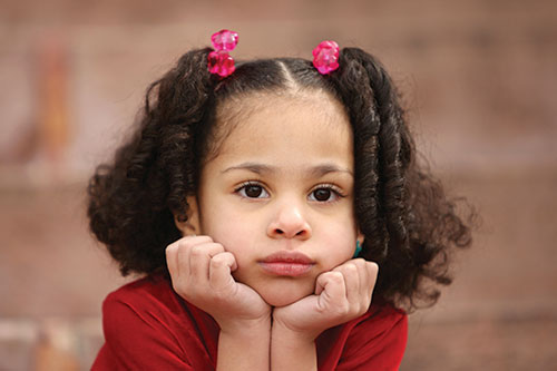 Little girl in time out thinking about consequences looking bored forlorn