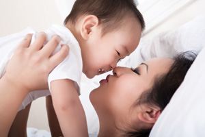 mother and baby enjoying motherhood holding up baby laying down smiling kissing