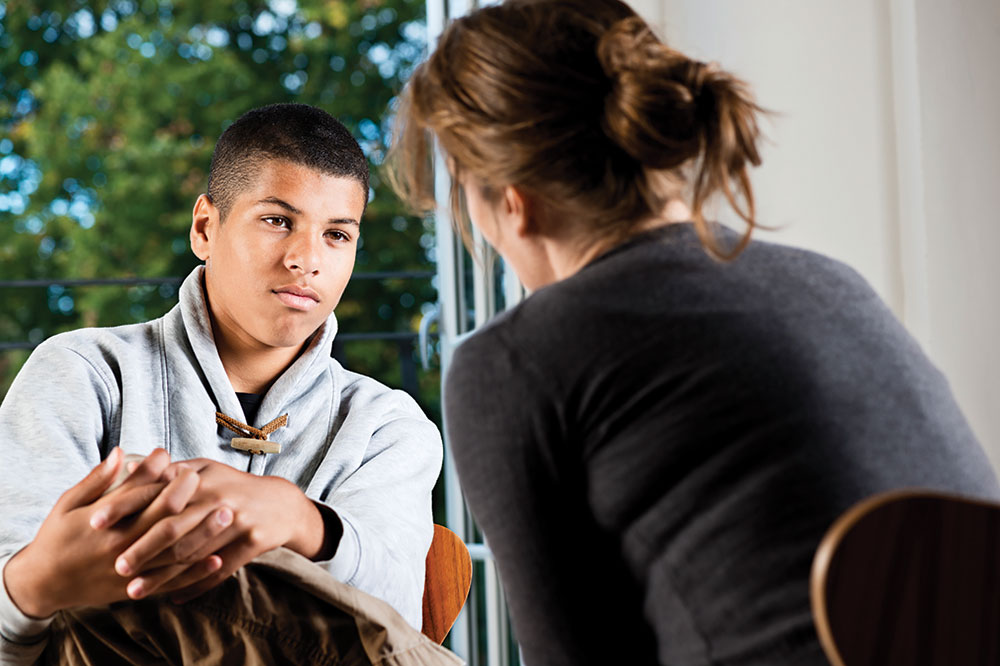 Should you hire a life coach for your teen? teen sitting in front of counselor looking rebellious