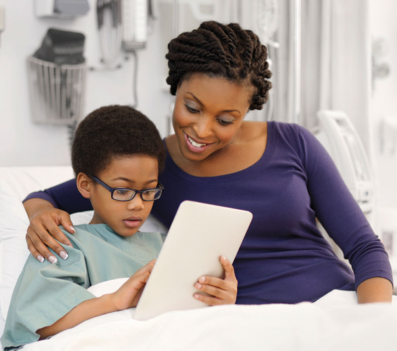 mother and son on hospital bed looking at tablet
