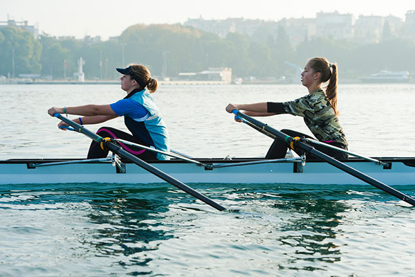 Winter workouts outdoor fitness rowing boat crew women on lake