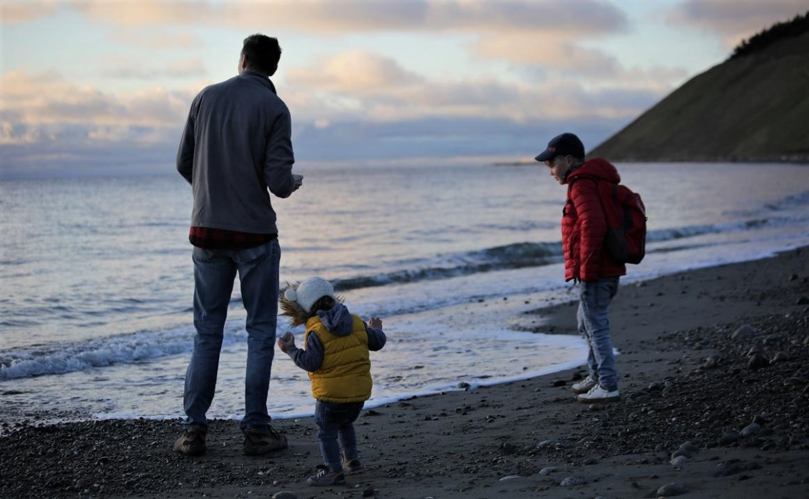 Dad and kids playing on a Washington beach before sunset with bluffs in the background 1000 hours outside challenge