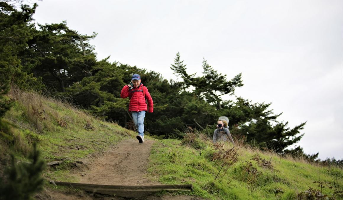 Boy in red jacket followed by father with baby in carrier on hiking trail in Washington mountains