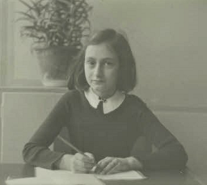 Anne Frank writing at a desk