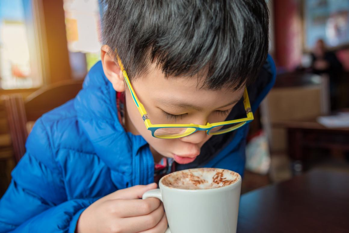 Boy-in-blue-jacket-sipping-hot-cocoa-after-ice-skating-winter-fun-kids-learning-to-skate