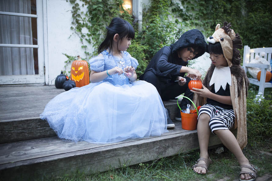 kids in costumes sorting candy