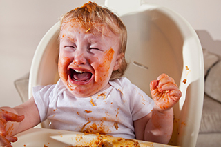 Crying baby eating food