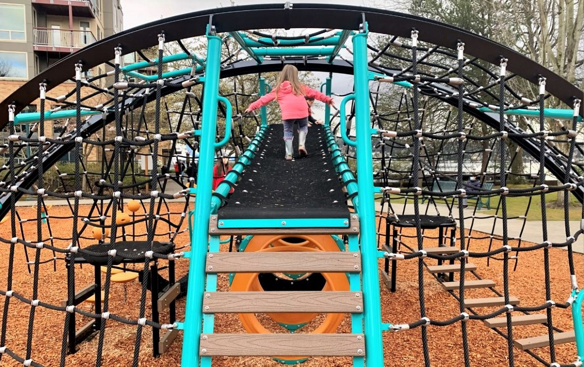Young girl in pink jacket on large rope climber at new Gene Coulon Memorial Beach Park playground in Renton near Seattle Washington
