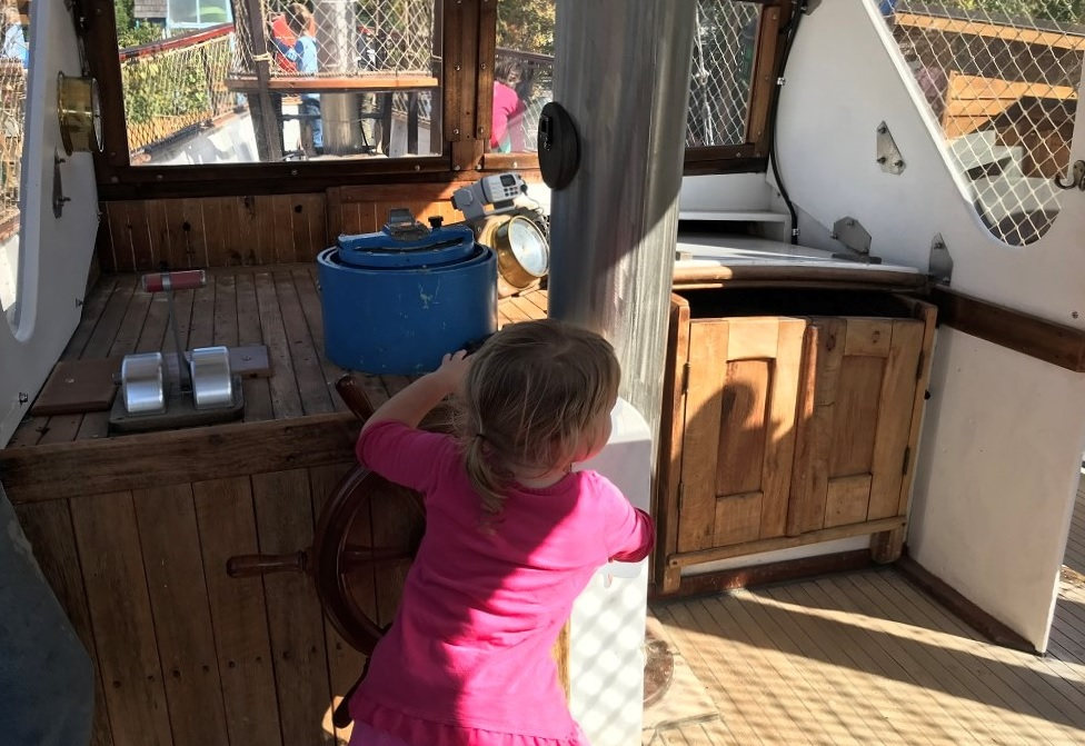 Girl-at-helm-vintage-schooner-Megan-D-Hands-On-Childrens-Museum-Olympia
