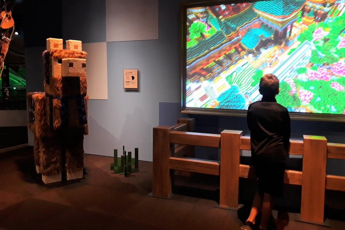 Minecraft-exhibit-llama-and-young-visitor-playing-large-screen-mopop-kids