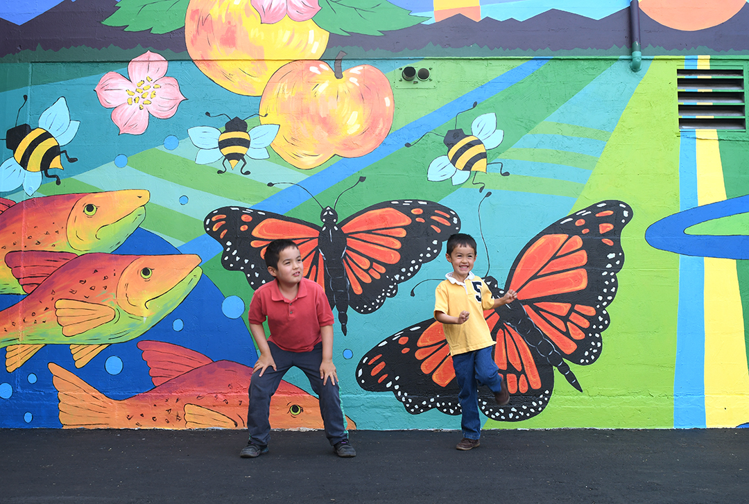 Colorful mural with boys in the foreground a Skagit Valley coop in Mount Vernon, Wash.