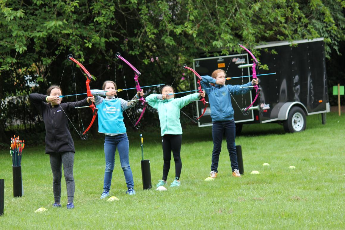 A group of young girls practice archery
