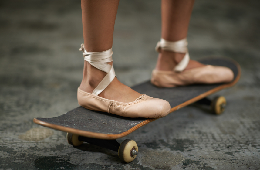 Girl with ballet slippers riding a skateboard