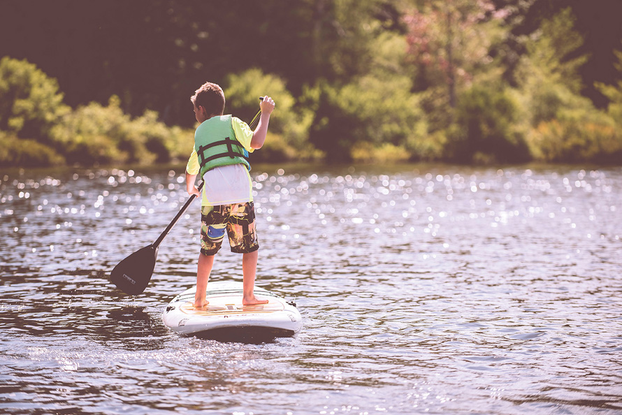 little boy paddleboarding