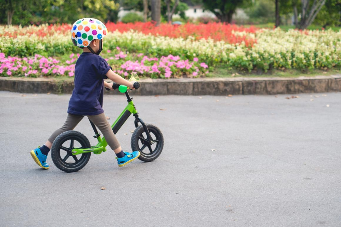 child-on-balance-bike-with-helmet-spring-tips-for-teaching-kid-to-ride-bike