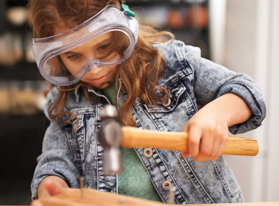 girl wearing safety goggles hammering a nail
