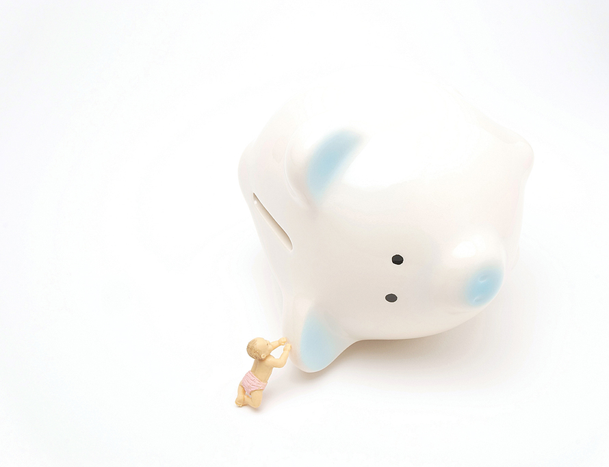 piggy bank tipped over with a plastic toy baby reaching toward it