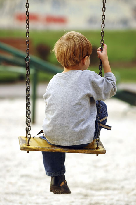 Lonely boy sitting on swing