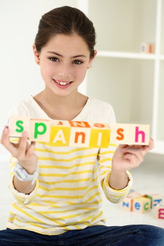 Young girl holding blocks that spell Spanish