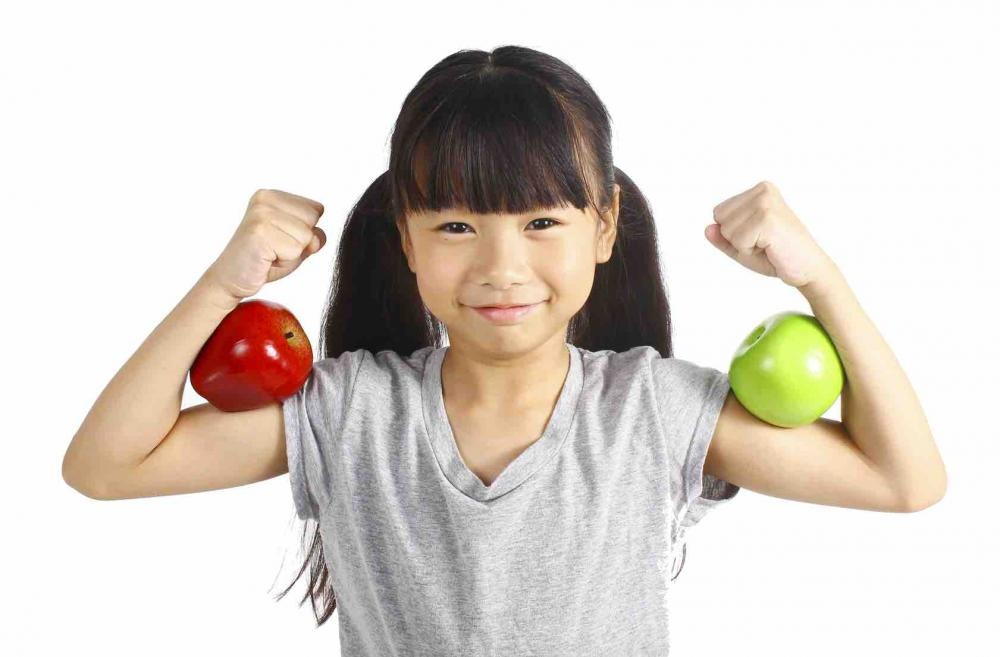 Little girl holding two apples in her elbows