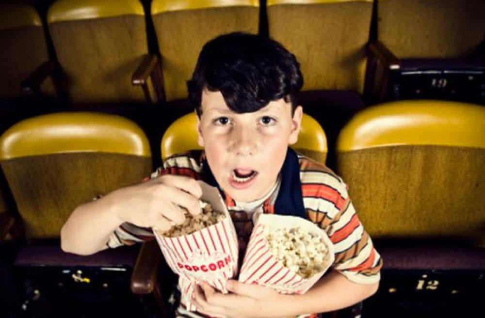 Boy watching a movie and holding two bags of popcorn