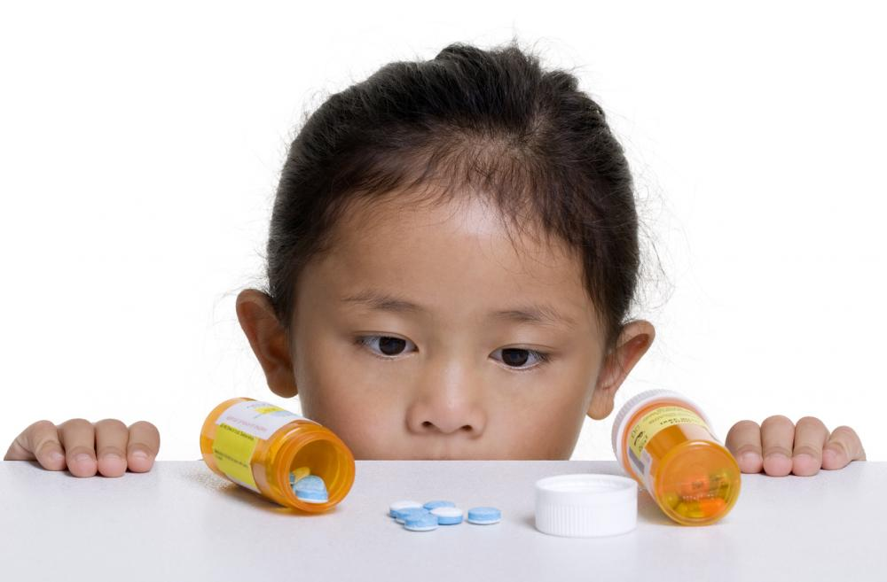 Kid looking at bottle of pills