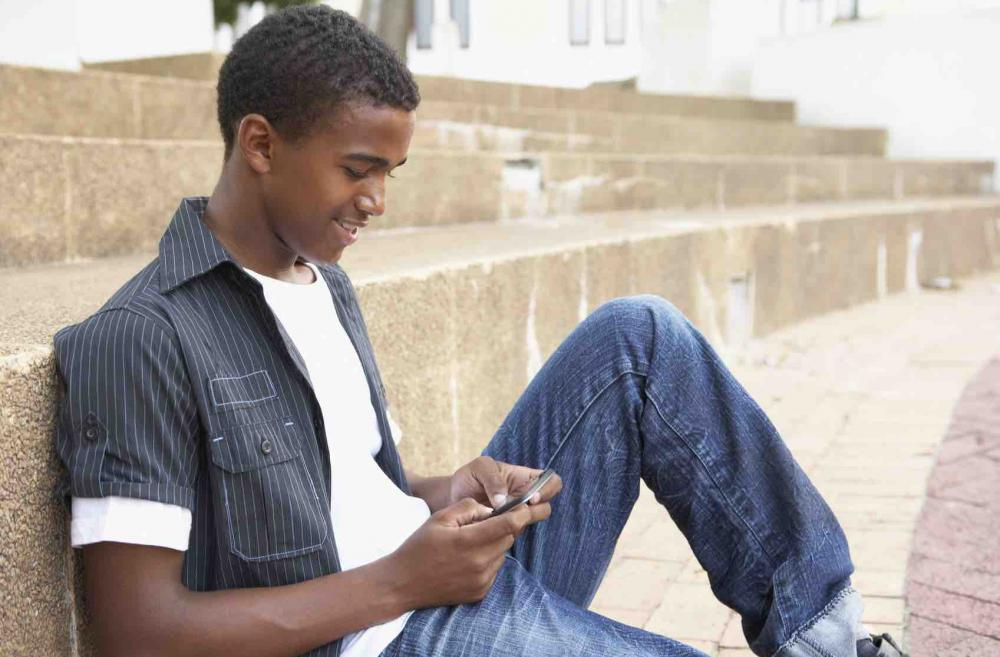 Teen boy typing on cell phone