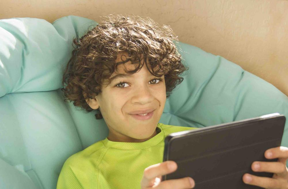 Curly-haired boy playing on tablet