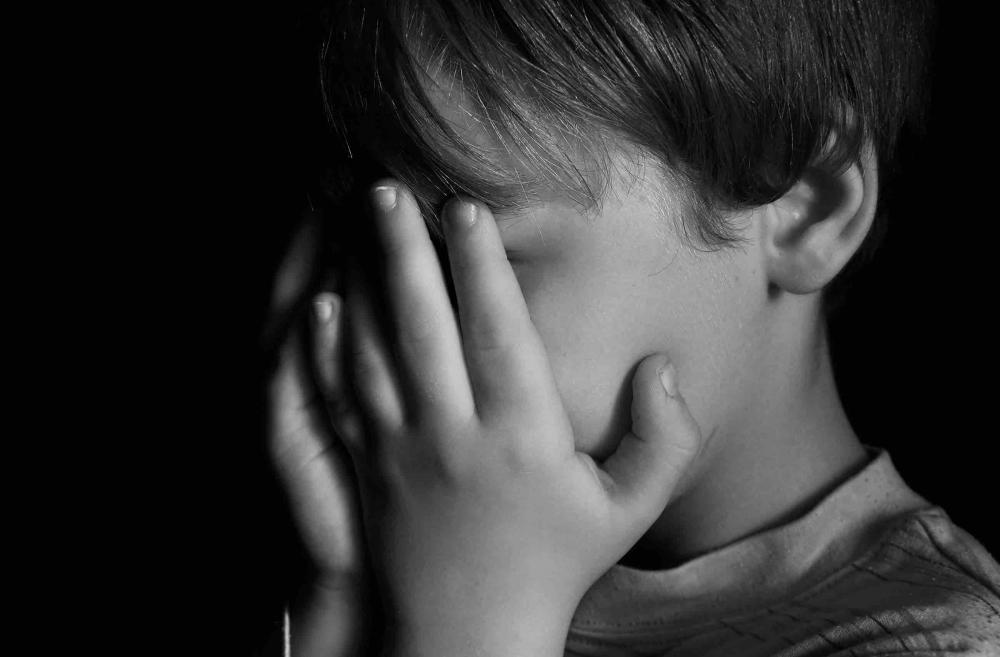 Black and white photo of an anxious little boy