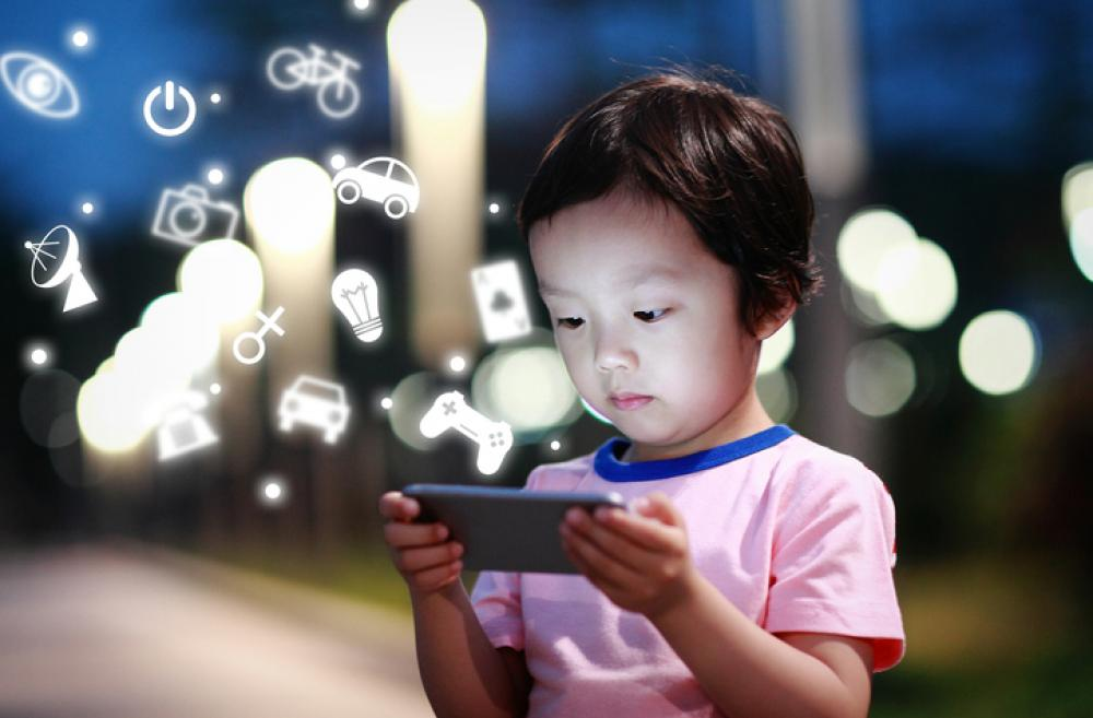 Child playing on phone outside