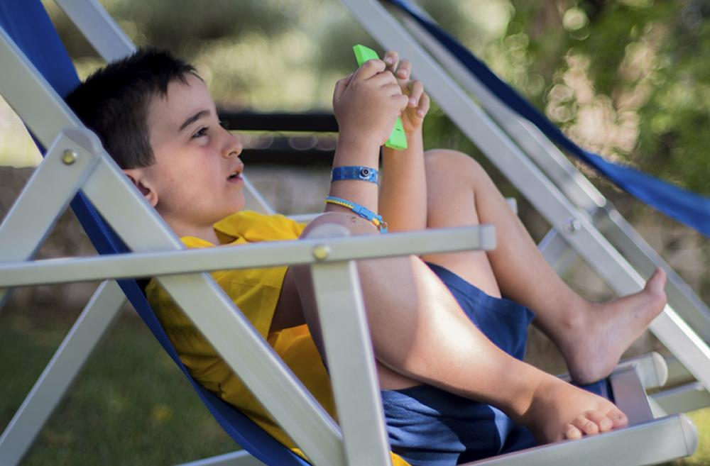 Boy outside with phone in lawn chair
