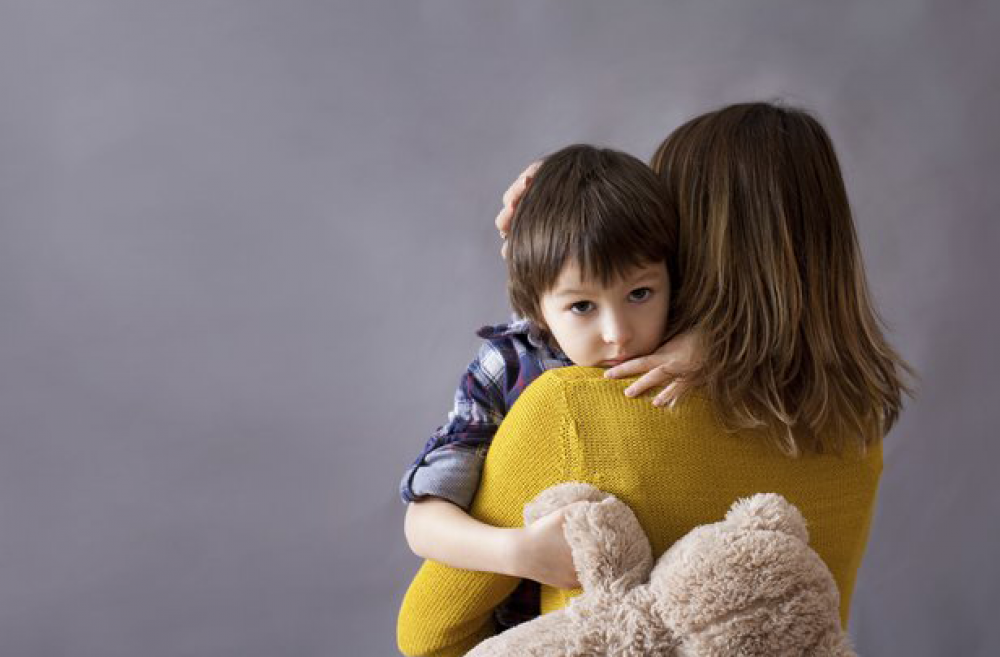 Sad boy holding mom tight with teddy bear
