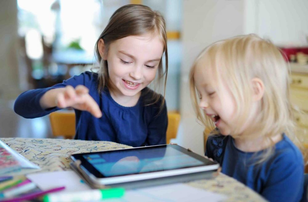 Two little girls playing on a tablet