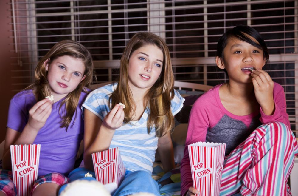 Three girls in pjs eating popcorn and watching a movie