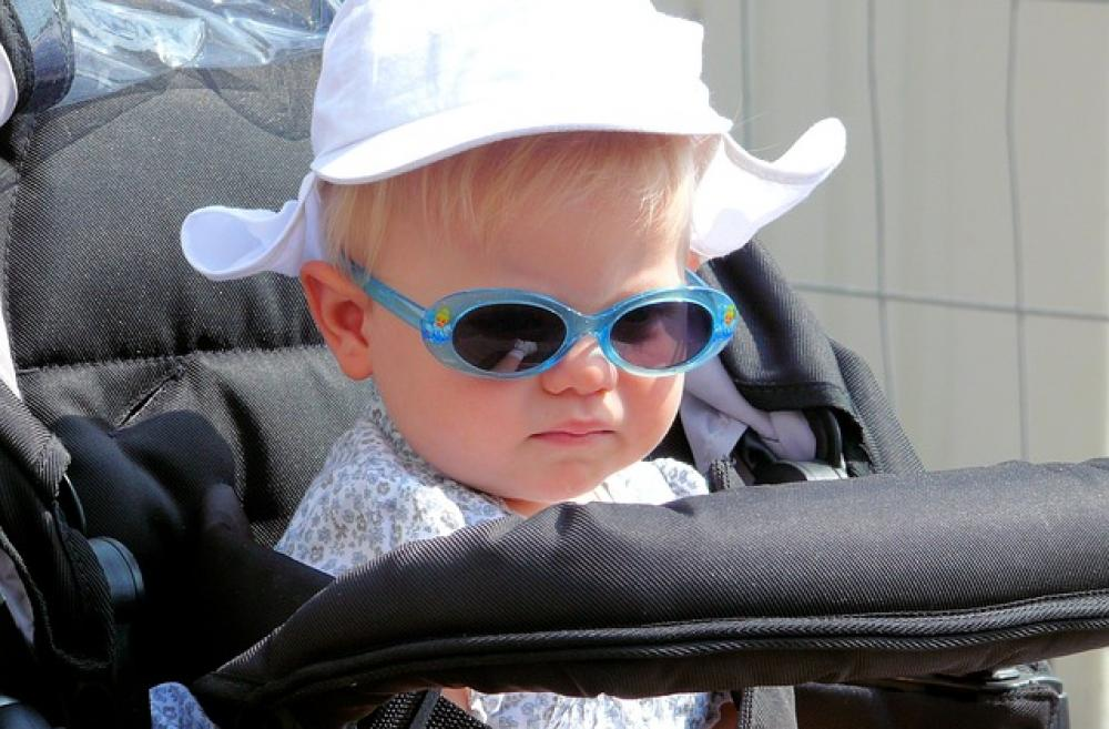 Baby with hat and sunglesses in stroller