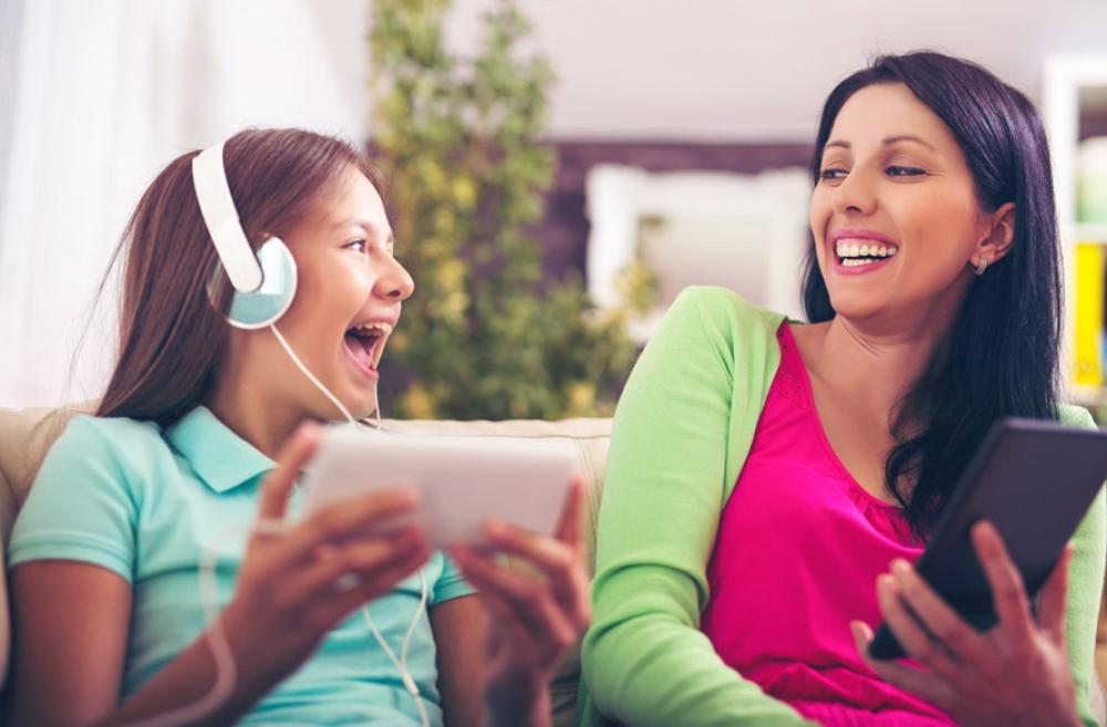 mother and teen daughter listening to a podcast