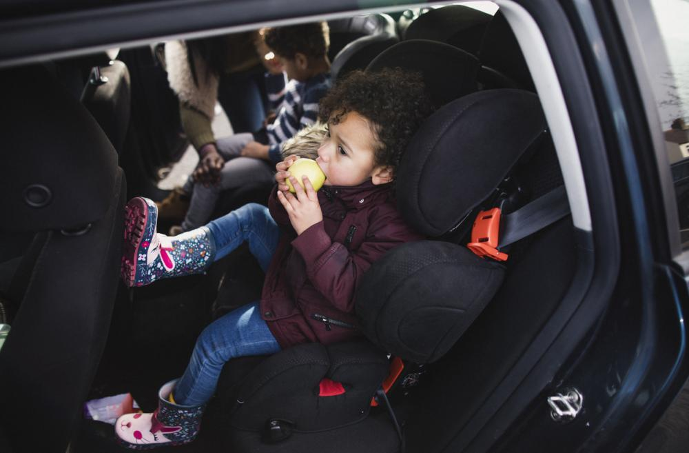 little boy eating an apple in the back seat of a car