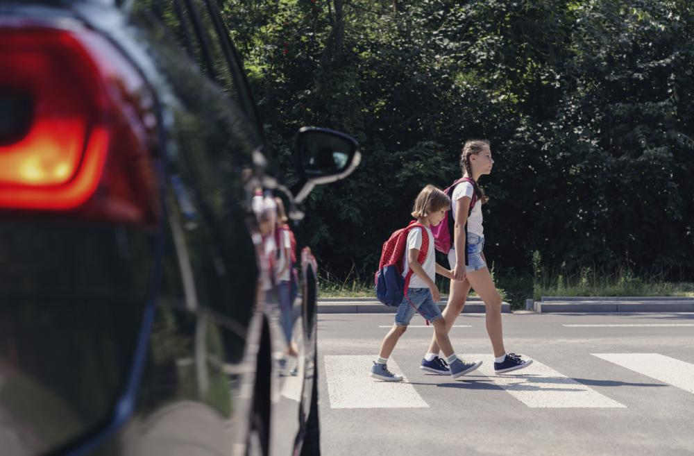 two school-age sisters crossing the street with a car waiting at a crosswalk