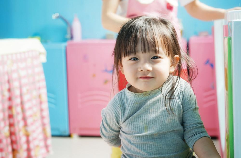 toddler girl looking at the camera with colorful background