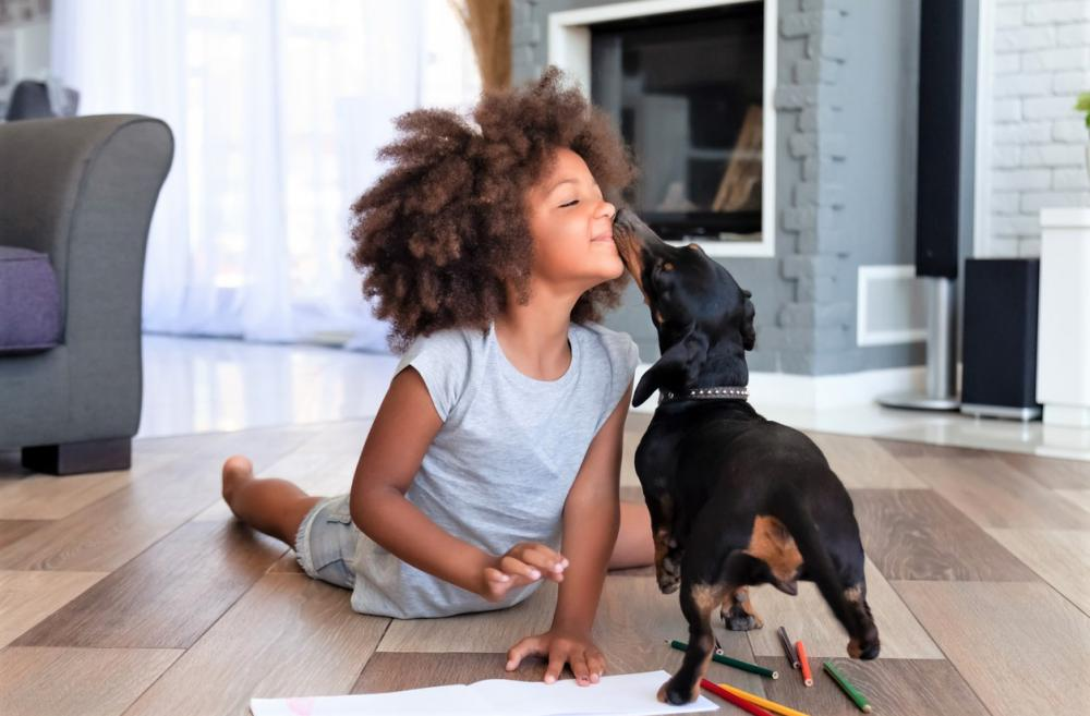 young girl on the floor with her small dog and art supplies