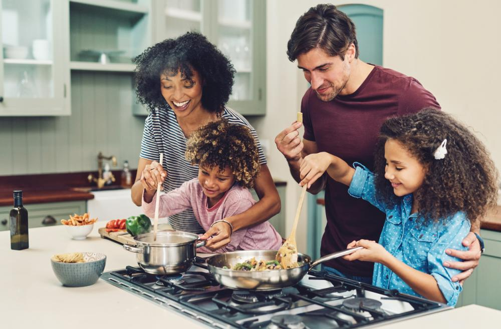 parents and two kids cooking together