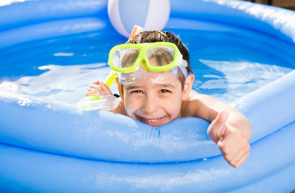 little boy wearing a snorkel in a pool in the backyard smiling at the camera