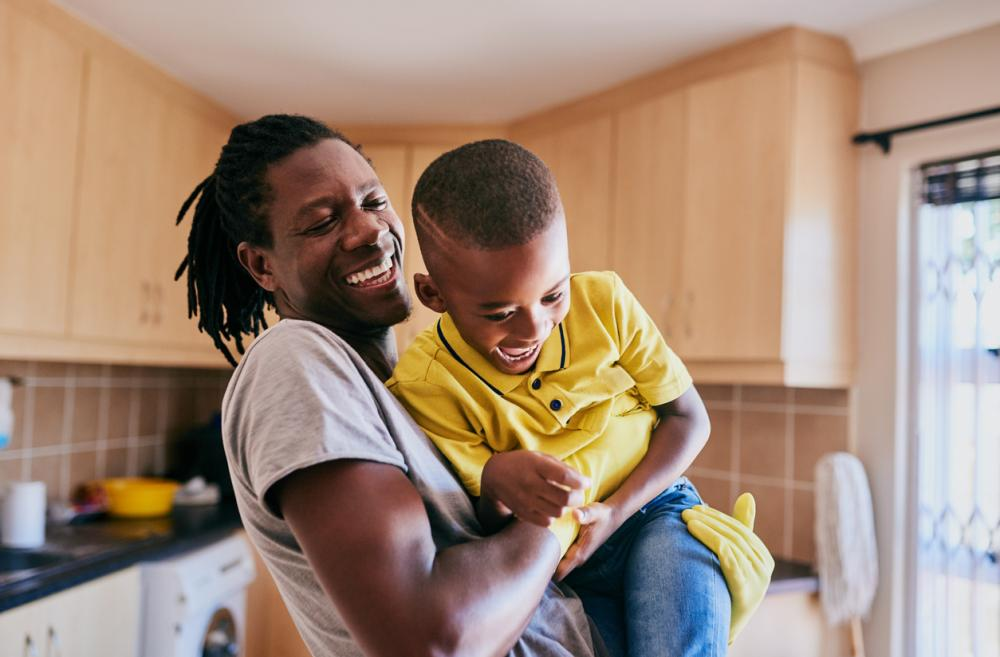 smiling black dad wearing rubber gloves and lifting up his laughing son